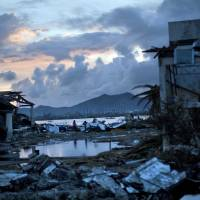 Unprecedented damage: Typhoon Haiyan survivors walk through the ruins of their neighborhood on the outskirts of Tacloban, central Philippines, on Wednesday | AP
