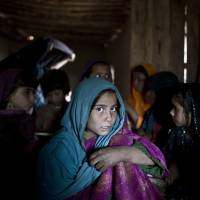 Education in exile: Afghan refugees attend a makeshift school in a mosque on the outskirts of Islamabad, Pakistan, on Thursday. Around a hundred illiterate children gather for three hours a day in a mosque room and a yard to learn from two volunteer teachers — a man and a woman — how to read and do numbers. | AP
