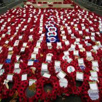 For the fallen: Poppy wreaths lie on the ground during a commemorative service on Armistice Day at the Cenotaph in central London, on Monday, in memory of Britain's war dead. In the run-up to Armistice Day, many Britons wear on their lapels a paper red poppy, which symbolizes the poppies that grew on French and Belgian battlefields during World War I | AFP-JIJI