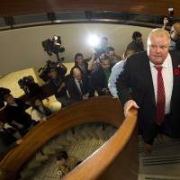 Cracks in the facade: A trail of reporters follow City of Toronto Mayor Rob Ford after he received his flu shot in the city Friday. According to Ford's lawyers, the embattled politician is considering entering a rehab program | AP