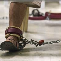 Eased restrictions: A detainee in restraints reads during a life skills class inside Guantanamo Bay, Cuba, in this March 2010 file photo. A military judge on Wednesday ordered the U.S. government to hand over correspondence on conditions at the prison and lifted restrictions on lawyers' communications with detainees | AFP-JIJI