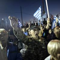 To the right: Supporters of ultranationalist party Golden Dawn wave Greek flags and shout slogans during an Oct. 26 rally in Athens | AFP-JIJI