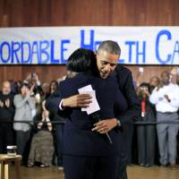 Hugs for health: President Barack Obama hugs a woman before speaking with volunteers who helped people sign up for health care on the <A HREF='http://HealthCare.gov' TARGET='_blank'>HealthCare.gov</A> site Wednesday in Dallas   AP