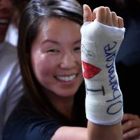 Perfect casting: A woman reacts after U.S. President Barack Obama autographed her cast, which reads 'I (heart) Obamacare,' in Boston on Wednesday | AFP-JIJI