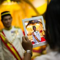 Strike a pose: A man takes pictures of a 'Datuk,' a self-styled Malaysian royal, before a private event at a palace in Gombak, on the outskirts of Kuala Lumpur, on Sept. 7. For centuries, the Malaysian royal title of Datuk, — the country's equivalent of 'Sir,' was a high honour that unlocked doors to the elite. But Datuks don't feel so special these days | AFP-JIJI