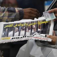 Jailed: A vendor sells a copy of a morning newspaper fronted by pictures of the trial of ousted Egyptian President Mohammed Morsi in Cairo on Tuesday. The headline reads: 'Morsi and his brothers in prison.' After four months in secret detention, Egypt's deposed Islamist president defiantly rejected a court's authority to try him Monday, saying he was the country's 'legitimate' leader and that those who overthrew him should face charges instead | AP
