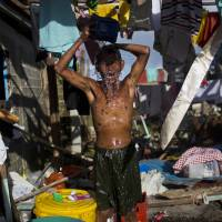 Water woes: A survivor of Typhoon Haiyan bathes in the ruins of his home in Guiuan, the Philippines, on Friday. Typhoon Haiyan, one of the most powerful storms on record, hit the country's eastern seaboard Nov. 8, leaving a wide swath of destruction.   AP