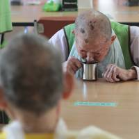 Patient resolve: A former South Korean leprosy patient drinks water at Sorokdo National Hospital on Sorok Island, South Korea, on Nov. 4. The island, once known as a place where hospital workers beat the leprosy patients exiled there and forced them into harsh labor, sterilizations and abortions, has become a peaceful refuge for many after years of discrimination and hardship and the only place they feel at home. | AP