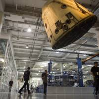 Looking up: Employees walk beneath a Dragon spacecraft hanging from the ceiling on the factory floor at rocket manufacturer SpaceX on Oct. 21 in Los Angeles. | THE WASHINGTON POST