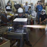 Blast, on: XCOR Aerospace test engineer Geoff Licciardello (center) conducts a test-firing of the 3N22 RCS rocket engine as his coworkers look on at Mojave Air and Space Port on Oct. 23 in Mojave, California. | THE WASHINGTON POST