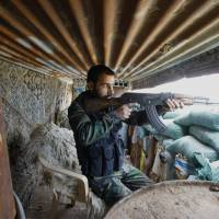 Firefight: A Shiite fighter from a group called the Hussein Brigade fires his weapon during clashes with rebels from the Sunni-dominated Free Syrian Army in the town of Hatita, in the Damascus countryside, on Friday. | AP