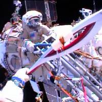Olympic feat: Cosmonauts Oleg Kotov and Sergei Ryazanskiy (rear) perform a handoff of the Sochi 2014 Winter Olympic Games Torch during a spacewalk outside the International Space Station on Saturday. The torch also visited the ISS ahead of the 1996 Summer Games in Atlanta and the 2000 Olympic Games in Sydney, but this is the first time it has been along for a spacewalk   AFP-JIJI
