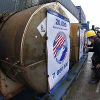 Atoms for peace: Representatives of participating companies sign containers with uranium to be used as fuel for nuclear reactors, prior to loading them aboard Atlantic Navigator ship in St. Petersburg, Russia, on Thursday. A 20-year program to convert highly enriched uranium from dismantled Russian nuclear weapons into fuel for U.S. power plants has ended, with the final shipment loaded onto a vessel in St. Petersburg's port on Thursday. The U.S. Energy Department described the program, commonly known as Megatons to Megawatts, as one of the most successful nuclear nonproliferation partnerships ever undertaken | AP