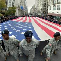 Forget the 50 states: Members of the New York State National Guard carry a large flag during the annual Veterans Day Parade on Monday on Fifth Avenue in New York City. An author says the U.S is really made up of 11 distinct 'nations.' |  AFP-JIJI