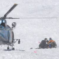 Search and retrieve: The body of one of the seven climbers killed by an avalanche is prepared to be flown off Mount Masago in the Tateyama range, Toyama Prefecture, on Saturday. | SHINANO MAINICHI SHIMBUN/KYODO