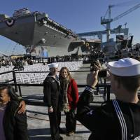 Finely crafted: A couple are photographed in front of the U.S. Navy's newest nuclear powered aircraft carrier, the USS Gerald R. Ford, during its christening in Newport News, Virginia, on Saturday | AP