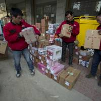 They love logistics: Delivery men sort through parcels from an online shopping portal in Beijing. Chinese Communist Party leaders on Tuesday gave an unusually strong endorsement of private companies as 'important components' of the economy | AP