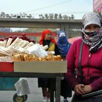 Life goes on: Uighur women shop at a bazaar in Hotan in China's far-flung Xinjiang region on Nov. 6. The Muslim Uighurs of Hotan say violence is being driven not by global jihadism, but a litany of police brutality, official discrimination and cultural repression | AFP-JIJI