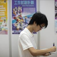Job journey: A Chinese job seeker fills out an application form at a job fair in Hong Kong in July. | BLOOMBERG