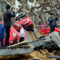 Deadly blast: Passers-by take photos Sunday in the Chinese city of Qingdao, where an oil pipeline exploded Friday, ripping roads apart, turning over cars and sending thick black smoke billowing over the city. | AFP-JIJI