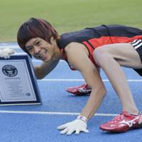Kenichi Ito poses for photographers with a Certificate of the Guinness World Records after setting the Guinness World Record fastest time for the 100-meter dash on his arms and legs on a race course at Komazawa Olympic Park Stadium in Tokyo Thursday. | AP