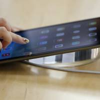 Brand new Pad: An employee demonstrates an Apple Inc. iPad Air tablet at the Apple Store Ginza in Tokyo on Nov. 1. | BLOOMBERG