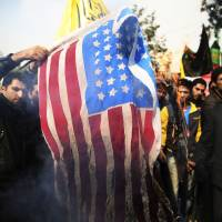 Iranian protesters burn a U.S. flag during an anti-American rally in Tehran on Nov. 4.  Iranian officials said Sunday the country made progress with world powers during 'serious' talks over Tehran's nuclear program, but insisted the nation cannot be pushed to give up uranium enrichment.   AP