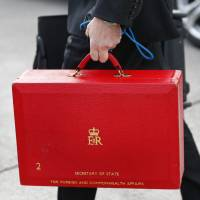 Red alert: A staff member carries a case for British Foreign Secretary William Hague after his arrival Saturday at Geneva International Airport for talks on Iran's nuclear drive.   AP