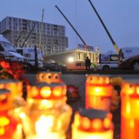 For the fallen: Candles and flowers are laid outside the collapsed Maxima supermarket in Riga on Friday. The reason for the collapse that killed at least 52 people during shopping rush-hour Thursday was still not known, but rescue and police officials said possible theories include architectural design flaws and shoddy construction work. | AP