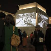 The dark side: People view photographs by Greg Constantine showing the plight of Myanmar's Rohingya projected Monday on the exterior walls of the Holocaust Memorial Museum in Washington | AP