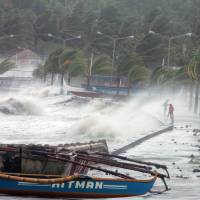 Trampling tempest: Residents stand near a seawall as deadly Typhoon Haiyan unleashes its wrath Friday on the city of Legaspi in Albay province south of Manila.  | AFP-JIJI