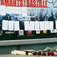 Deadly blast: Flowers lie in front of a poster of the musical '1789, The Lovers of Bastille,' in Paris on Saturday, after an explosion at a rehearsal for the show killed one person and wounded 15 others | AFP-JIJI