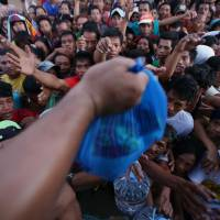Hands out: Survivors struggle to grab relief goods from a private group in the typhoon-hit city of Tacloban, in the central Philippines' Leyte province, on Monday. | AP