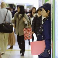 Manhunt: A policewoman (right) stands guard near the entrance of JR Funabashi Station in Chiba Prefecture. | KYODO