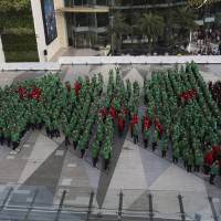 One for the ages: Wearing red, green and black hoodies, 852 Thai schoolchildren wave as they break the Guinness world record for forming the largest human Christmas tree in Bangkok on Friday. One of the country's largest shopping malls arranged the publicity stunt, in which the participants outdid the previous record set by 672 people in Germany in 2011. | AP