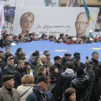 Stating their case: Tens of thousands of demonstrators carry EU flags as they march to demand that the Ukrainian government reverse course and sign a landmark agreement with the European Union in defiance of Russia, as they pass by a poster of former Ukrainian Prime Minister Yulia Tymoshenko (left) and opposition leader Arseniy Yatsenyuk, in Kiev on Sunday. The words on the poster read, 'We must fight for independence.' | AP
