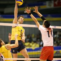 Soaring above: Brazil's Bruno Rezende attacks against Japan's defense, including middle blocker Yoshihiko Matsumoto, on Friday in the FIVB Men's Grand Champions Cup in Tokyo. Brazil defeated Japan 25-17, 25-23, 25-18. | FIVB