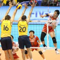 Working together: Three Brazilians form a blockade as Japan's Yu Koshikawa spikes the ball during Friday's FIVB Men's Grand Champions Cup. | FIVB