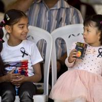 Fallen idols: Children who lost relatives in the terrorist attack on Nairobi's upscale Westgate Mall wear black ribbons during a memorial service in the Kenyan capital marking the one-month anniversary of the Sept. 21 strike by militants. | AP