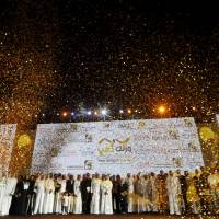 Monetizing flab: Participants in Dubai's Your Weight in Gold challenge stand on stage during the final weigh-in Thursday in the United Arab Emirates. The competition promised 1 gram of gold for every kilogram shed, provided contestants had lost a minimum of 2 kg by August 16, the end of the Muslim fasting month of Ramadan. | AFP-JIJI