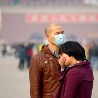 Palpable pollution: A visitor to Tiananmen Square in Beijing wears a face mask against dirty air as another covers her mouth on Nov. 5. | AFP-JIJI