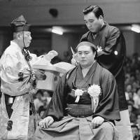 End of an era: Yokozuna Taiho gets his topknot removed in 1971.   KYODO