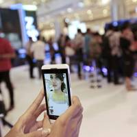 Self-obsession: A sales person takes a 'selfie' to demonstrate a mobile-phone camera, now an all-important tool of social media. Gary Vaynerchuk, CEO of VaynerMedia and social-media expert, claims that Instagram, Twitter, Facebook and the like have spawned a culture of self-aggrandizement through online bragging. | BLOOMBERG