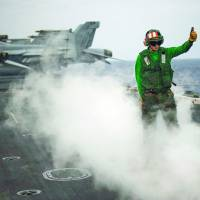 Coordinated effort: Flight operations are conducted aboard the USS George Washington on Wednesday during a joint drill with the Self-Defense Forces south of Japan. | REUTERS/KYODO