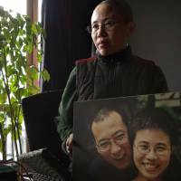 Festive chill: Liu Xia, the wife of jailed Chinese Nobel Peace Prize laureate Liu Xiaobo, poses with a photo of the pair at home in Beijing on Dec. 6, 2012. In recent years, Chinese authorities have imposed heavy prison sentences on well-known activists and dissidents around the Western Christmas holiday period. Liu Xiaobo's 11-year sentence for alleged subversion was handed down on Christmas Day in 2009. | AP