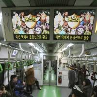 Addictive?: Ads for a mobile Internet game play on monitor screens in a subway train in Seoul on Wednesday. | AP