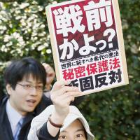 "Shades of a dark chapter?: A woman takes part in a public rally against the state secrets bill Monday in the city of Osaka, holding up a placard reading: ""Prewar era?""   