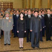 High profile: In this image released by North Korea's state media, leader Kim Jong Un and his wife, Ri Sol Ju, pose with high-ranking officials in Kumsusan Palace of the Sun in Pyongyang on Tuesday to mark the second anniversary of the death of Kim Jong Il. | AP