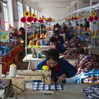 Hemmed in: Seamstresses work at the Sonbong Textile Factory Saturday inside North Korea's Rason Special Economic Zone. | AP
