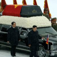 On the way out: Kim Jong Un (right) and his uncle, Jang Song Thaek (left), walk beside a hearse carrying the body of late North Korean leader Kim Jong Il in Pyongyang on Dec. 28, 2011. | AFP-JIJI